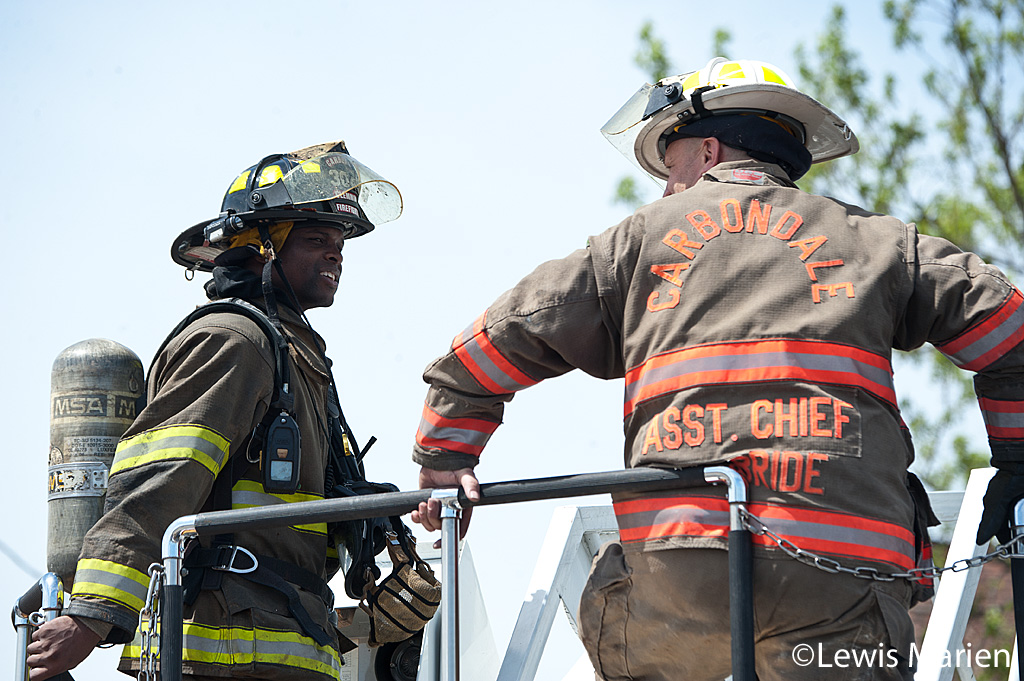 Carbondale Fire Department firefighter Wesley Clemmons (left) and Assistant Chief Stephen McBride talk after putting out a house fire at 208 W. Hospital Drive in Carbondale.