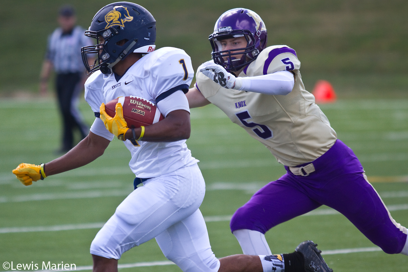 Carleton College's Chris Madden (1) runs with the ball as Knox College's Sam Coffey (5) closes in during the Prairie Fire's home opener against the Knights on Sept. 12 at Knox College's Stisser Field. The Prairie Fire defeated the Knights 23-20.