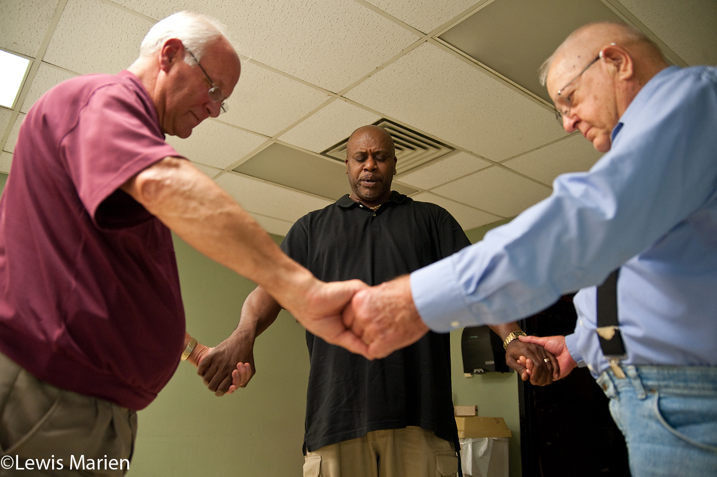 From left to right, Bob Clark, Greg Vickers Sr., and Roy Ewalt, all of Galesburg, Ill., pray at the conclusion of the first Bible study class on Sept. 14 at the Knox County YMCA in Galesburg, Ill.