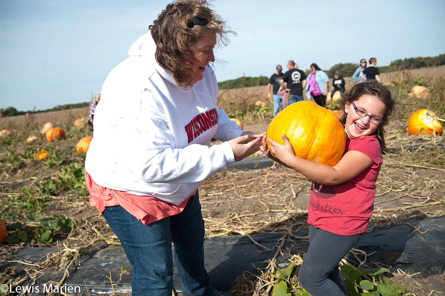 Julie McCurdy, left, of Moline, Ill., has a laugh while her daughter Macy, 5, struggles to carry a giant pumpkin on Oct. 10 during the Giant Pumpkin Festival at Country Corner Farm in Alpha, Ill.