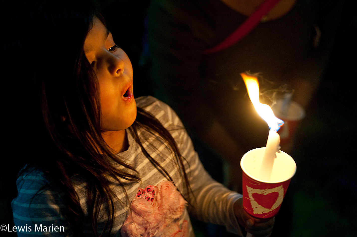 Gabby Nunes, 6, of Galesburg, Ill., tries to blow out her candle during the 22nd annual Take Back the Night Rally's candlelight vigil on Oct. 20 at the Lake Storey Pavilion in Galesburg, Ill.