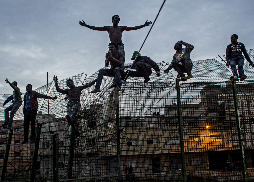 The Wall of Europe, Spain, 2014  Young Africans try to climb the double fence that separates Africa from Europe, near Beni Enza on the border of Spanish exclave Melilla   Photograph: Sergi Cámara