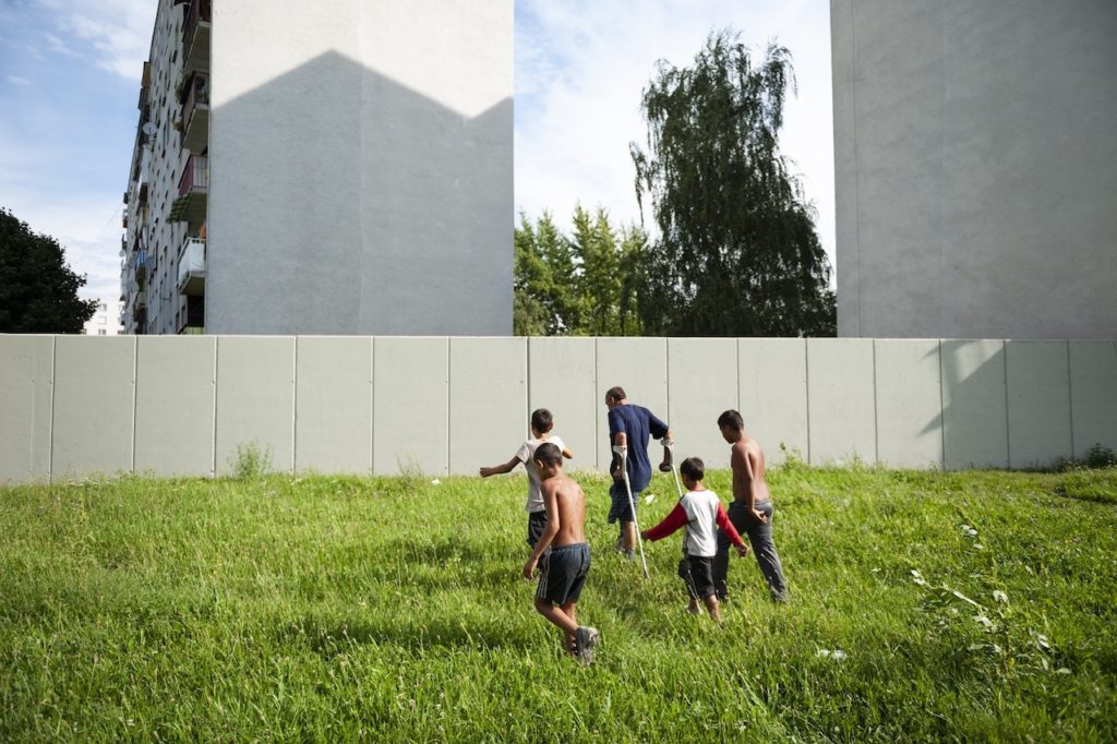 Roma Wall, Michalovce, Slovakia, 2010  A group of Roma walk towards a concrete wall in Michalovce, eastern Slovakia. About 50 families on a housing estate have financed its erection to separate the local Roma camp from their residential area   Photograph: Attila Balázs