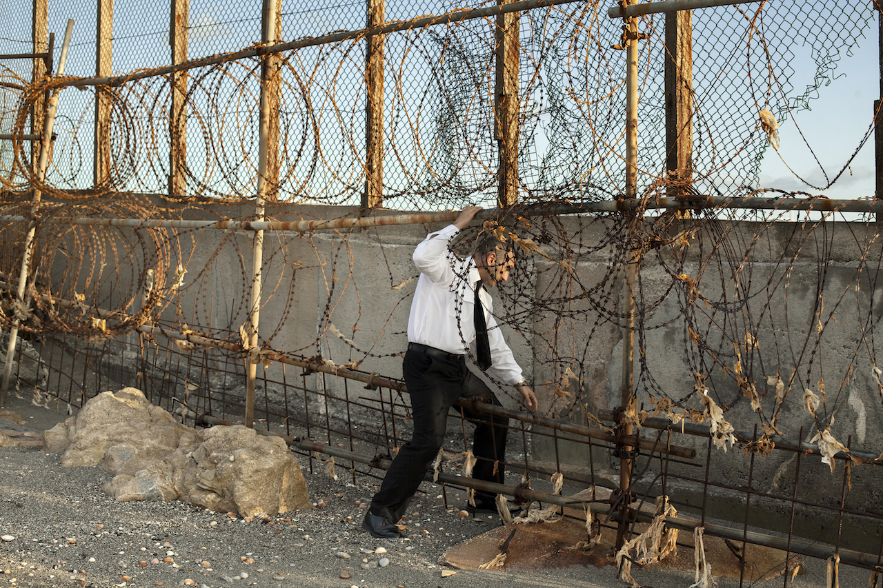 The Fence of Gibraltar, British Overseas Territory of Gibraltar, 2016  A British customs officer checks the hole made by tobacco smugglers in the border fence that separates the UK from Spain   Photograph: Arnau Bach