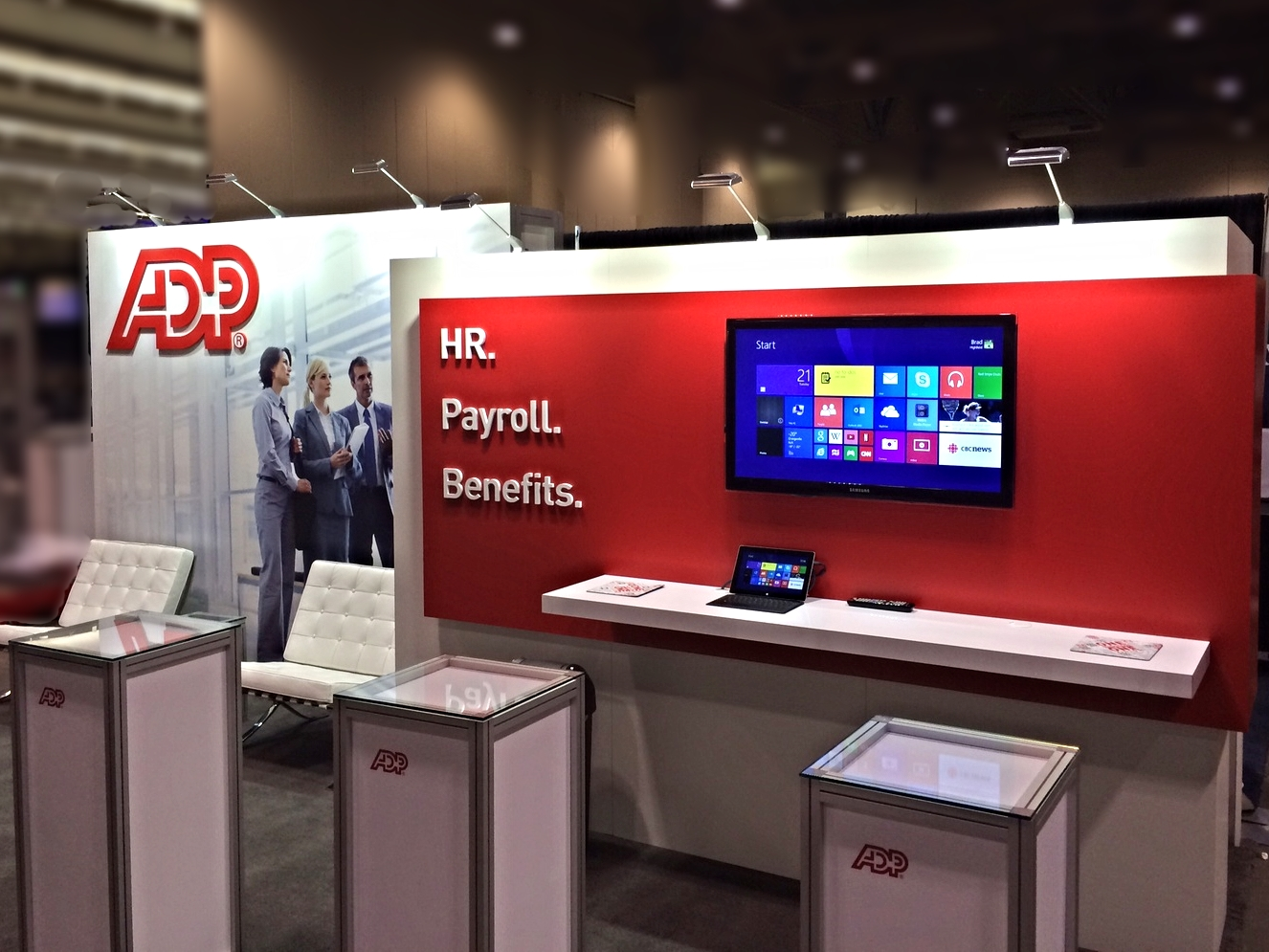 ADP Canada's red and white exhibition booth design is a combination of custom wall panels and our exhibit display system Octanorm.
