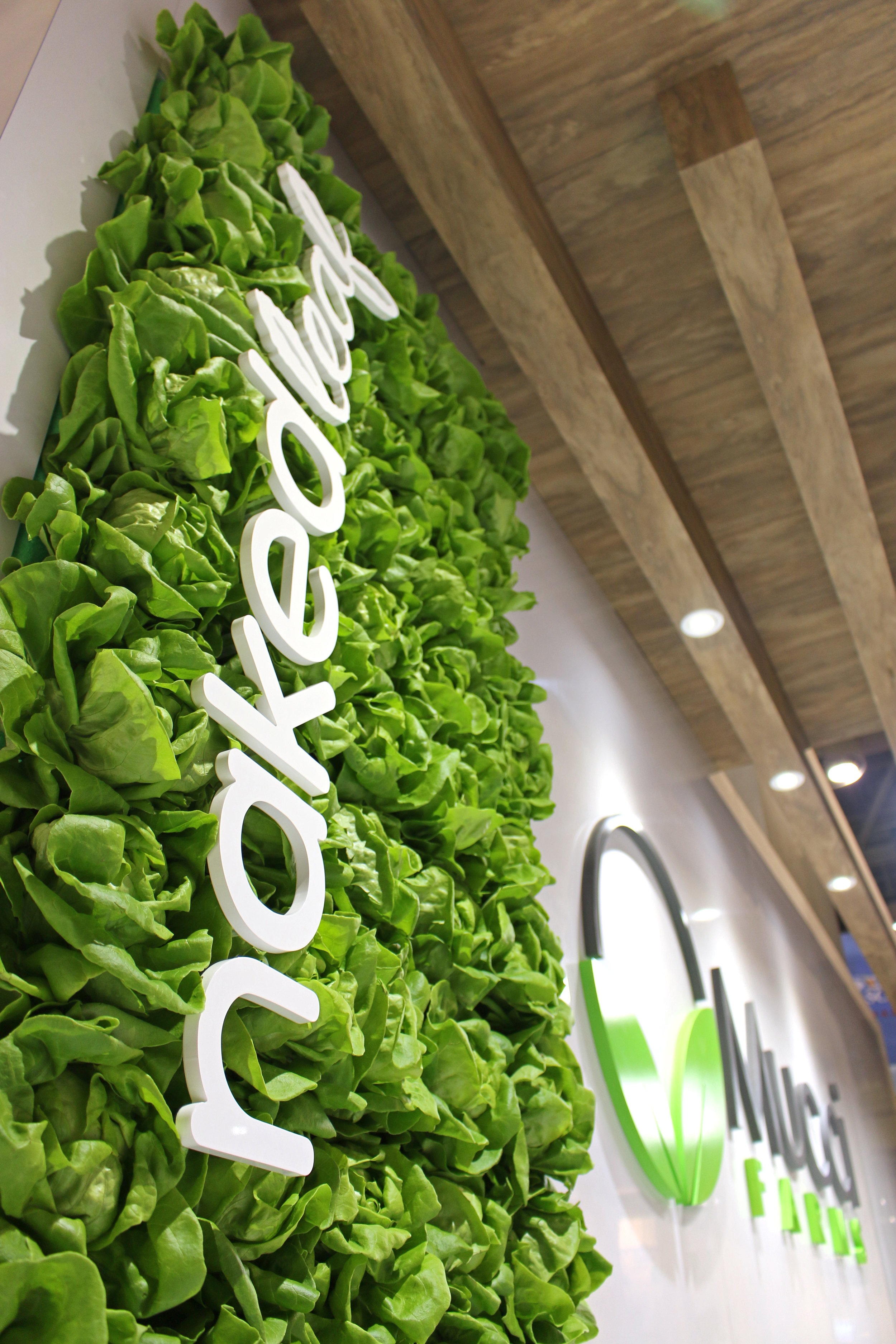 3-D LETTERING & LETTUCE WALL   16-foot-high towers provide the perfect backdrop for the use of dimensional lettering. Even at eye level the use of 3D logos is striking and contributes to the layers and depth of their design. We also integrated a custom wall featuring their 'Naked Leaf' living lettuce in water, with a painted acrylic logo nested within the leaves.