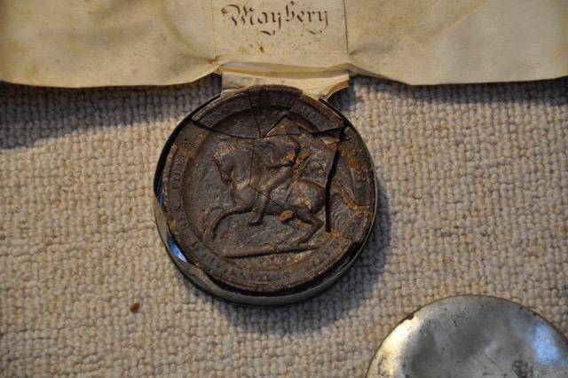damaged seal in metal container for the Manor of Hay