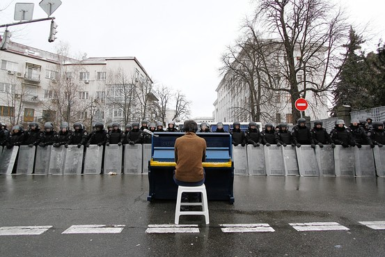 Markiyan Matsekh, performing before riot police in Kiev on a piano painted in the colors of Ukraine.  Künstlerhaus