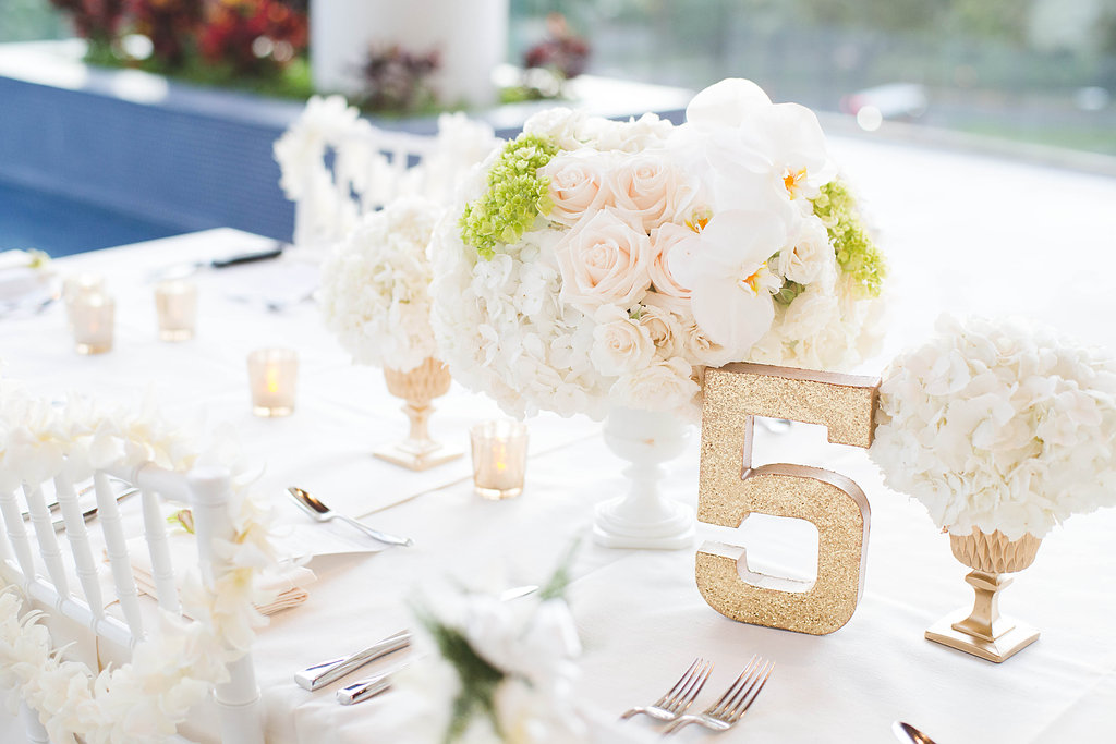 white centerpiece with gold table number by Passion Roots | Ashley Goodwin Photography | Passion Roots