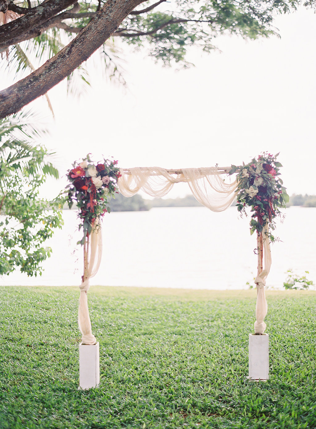 romantic berry and wine flowers with fabric draping on ceremony arch by Passion Roots | The Great Romance Photography | Oahu, Hawaii