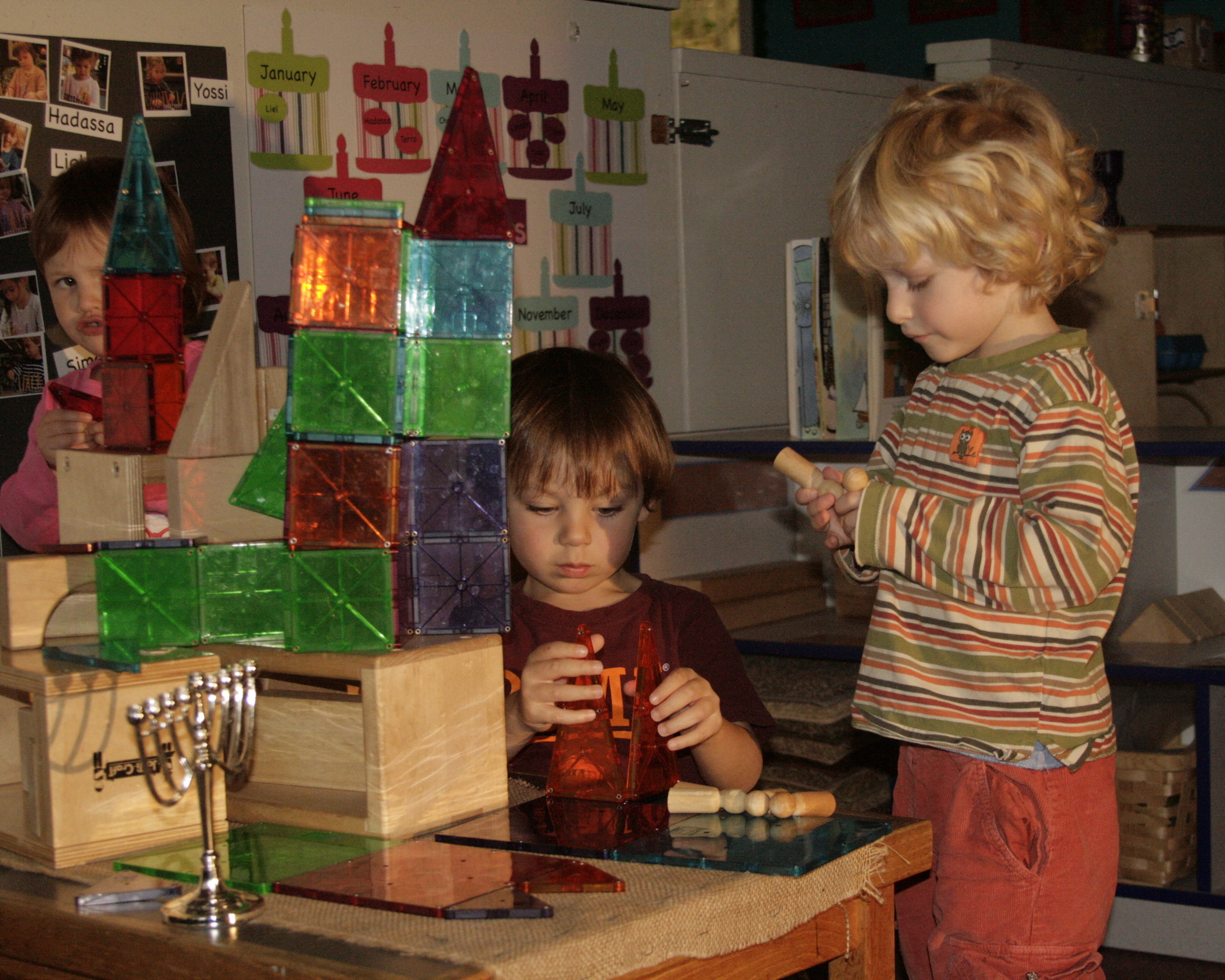 Explorer students explore light and shadow with the magna-tiles, blocks and a light projector.