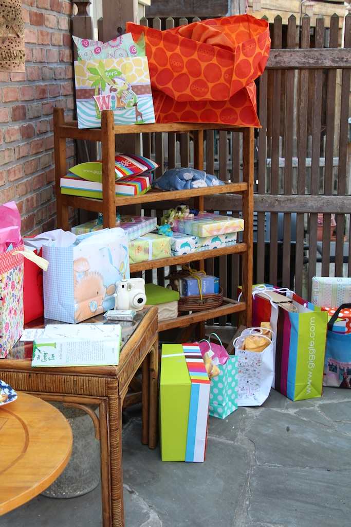 Use what you have!   Rather then placing all of the shower gifts on the ground, or buying a table for them to sit on, I rolled the bakers rack from our kitchen (the piece that normally held some of our dishes) outside and arranged the gifts. This made for a festive gift display that added to the outdoor party vibe.