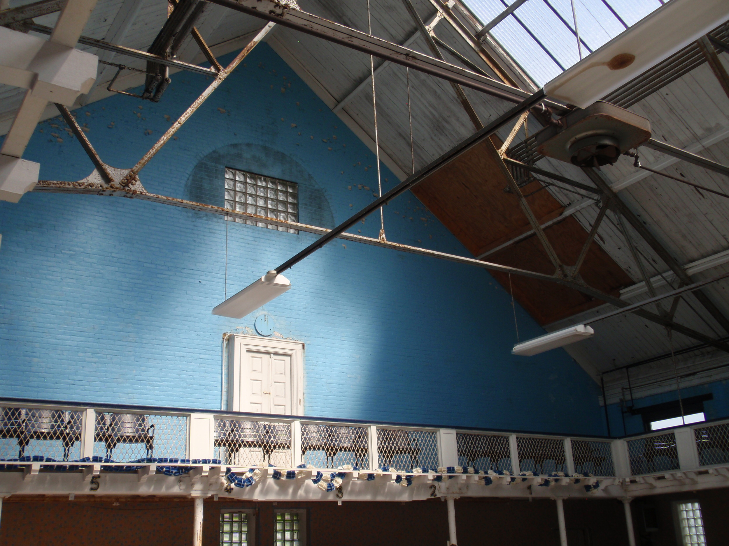 The western end of the pool. A large semi-circle window had been here, but was replaced with glass blocks in the 1970s. The door provides access to an outdoor catwalk that was over the original outdoor pool.