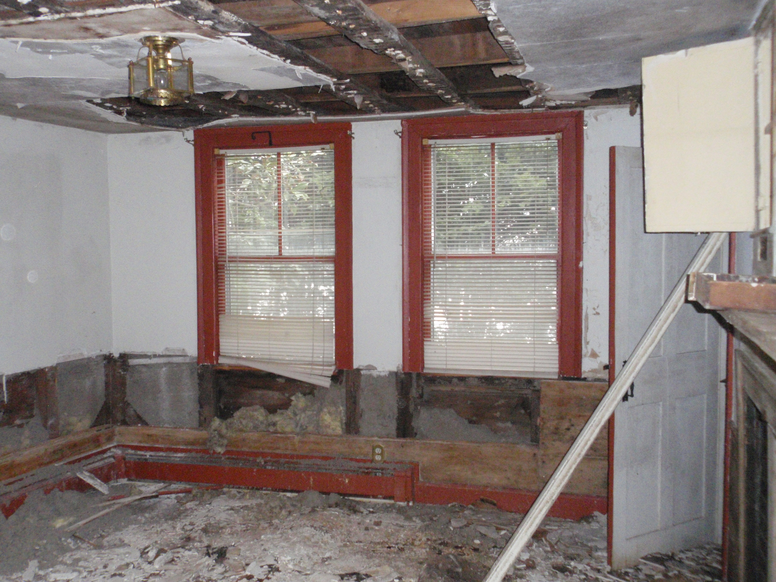 The historic kitchen has seen the most damage in the house. Original paneling has been pulled from the walls and some of the ceiling plaster has been taken down.