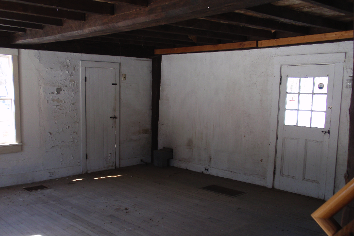 The original McFarland-Sanger House was only one room, roughly 13' by 18'. The heavy summer beam running down the middle of the room is just barely visible. The main entry door is behind the photographer.