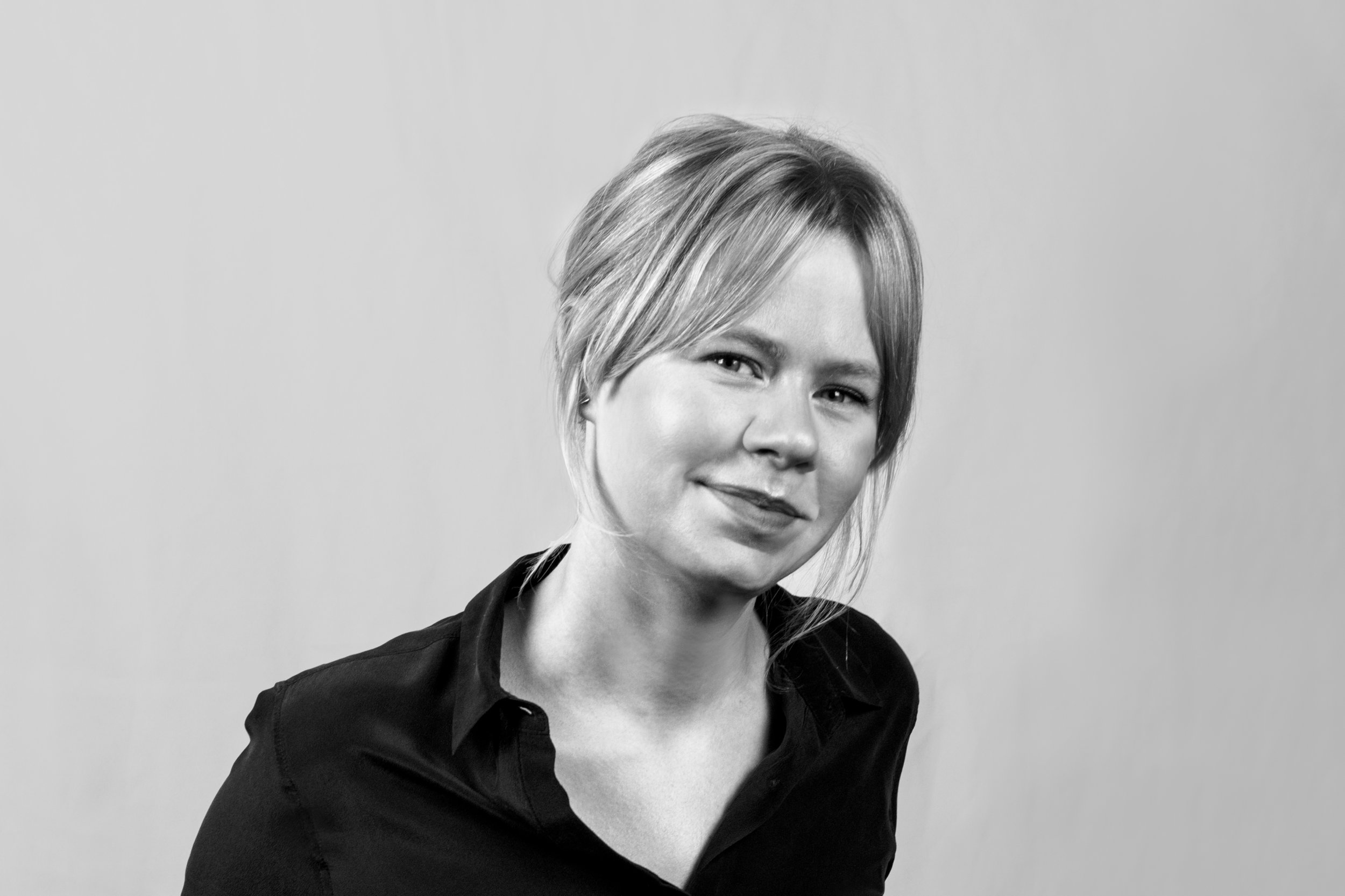 Black and white portrait of Lauren Race on a white background, wearing a black collared shirt.