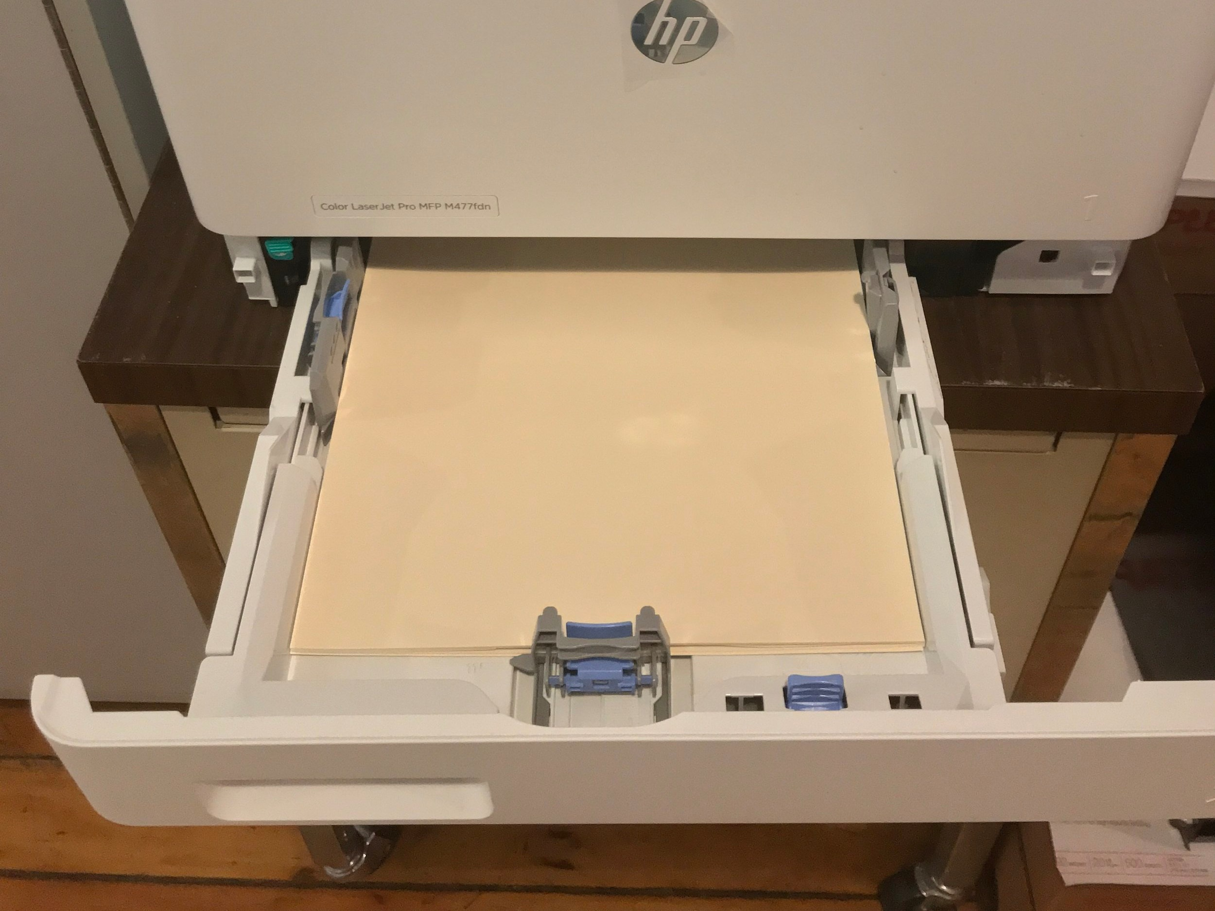Manual feed tray in a color laser printer ejected and loaded with Swell Touch Paper. Paper is loaded so that it prints on the sticky, coated side of the paper.