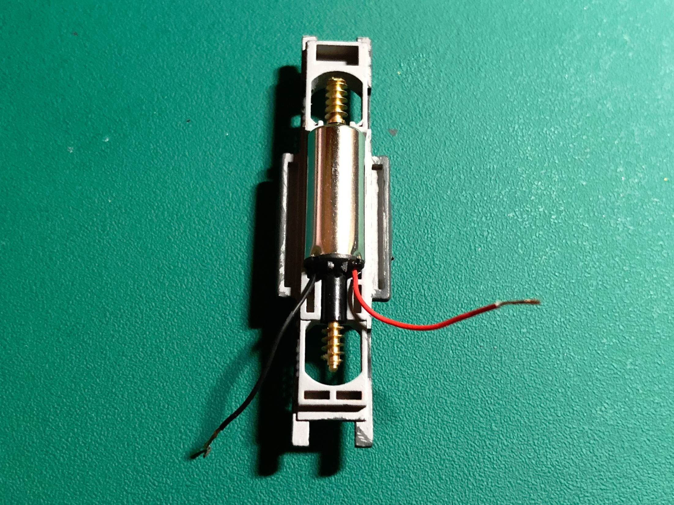 Step 20 - Insert the motor into the bottom frame. Orient the motor so that the red wire is on the right side of the frame. Notice that the rear of the frame has two long beams protruding outward. The front of the frame has a single rectangular depression.