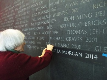 """Image Caption: Artist Ann Hawkins etches Julia Morgan's name into the black granite on thepantheon of the AIA National Headquarters. Julia Donoho, AIA, Esq. led the 2014 nominationprocess for Morgan, and also worked with the Venturi and Scott Brown nominating team. Donohosaid, """"This success for men and women working in partnership is a victory 47 years in themaking. A new story is being told about how creative collaboration can succeed. The work of Boband Denise is a weaving together of two great talents to create a body of work of lasting influenceon the profession. It was a privilege to be part of telling that story."""" Image Credit: Jack Evans"""