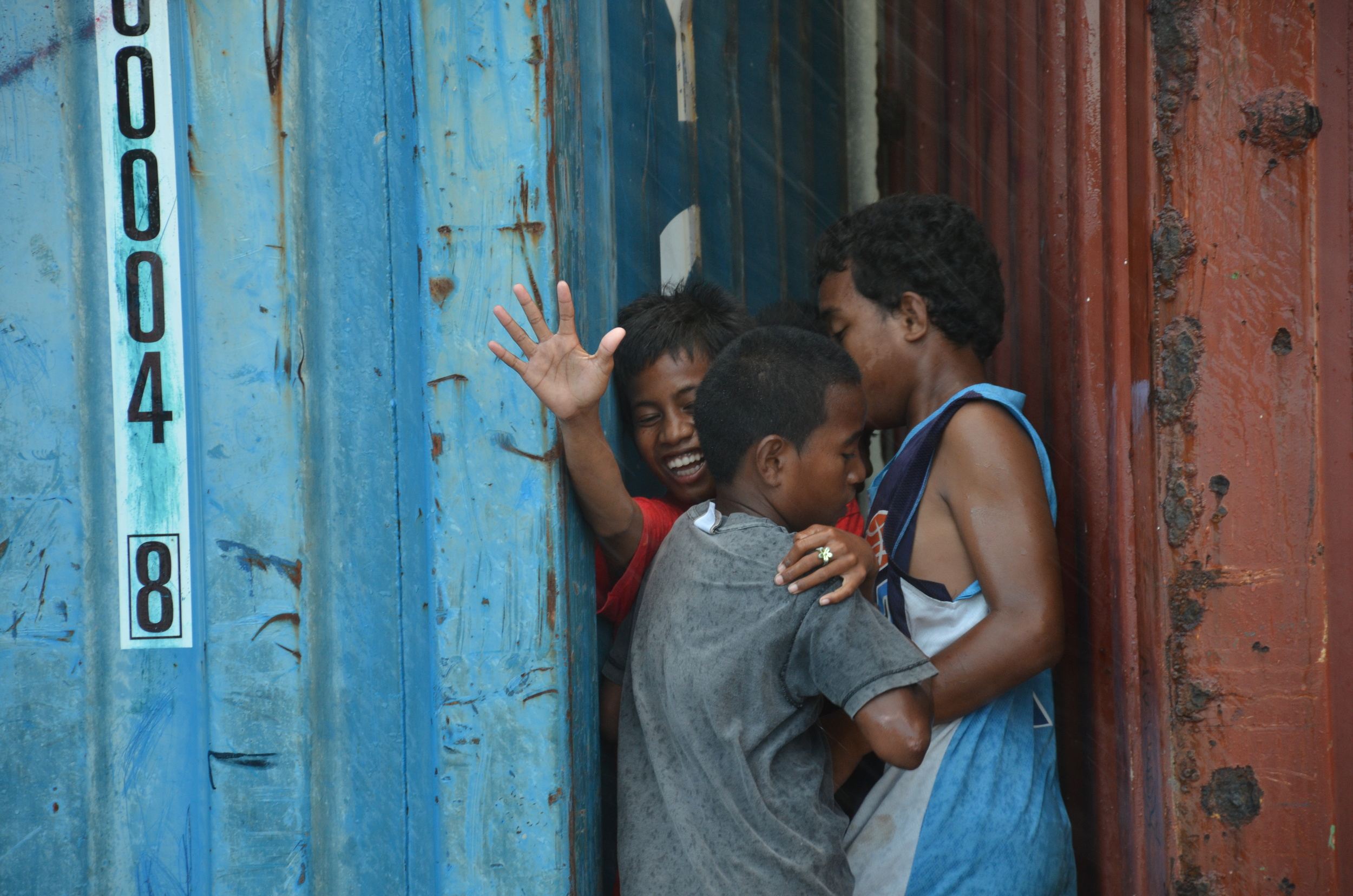 During a sudden rainstorm, children seek shelter between shipping containers.