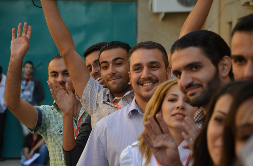 "Ministry of Culture employee Ali Makhzomy, 23, center with arms raised, participates in team-building exercises with other volunteers after auditioning to speak at the first TEDxBaghdad conference. The slogan for the conference, a satellite version of the California-born TED conference, was ""Make the impossible possible.""   (  Dan Zak/The Washington Post)"