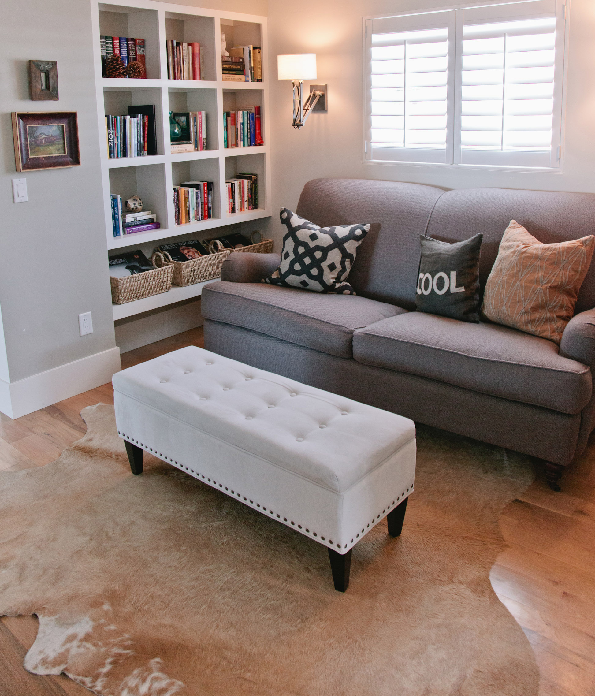 Built-in bookshelves surround a comfortable sofa and storage ottoman. The cowhide rug adds an eclectic touch.