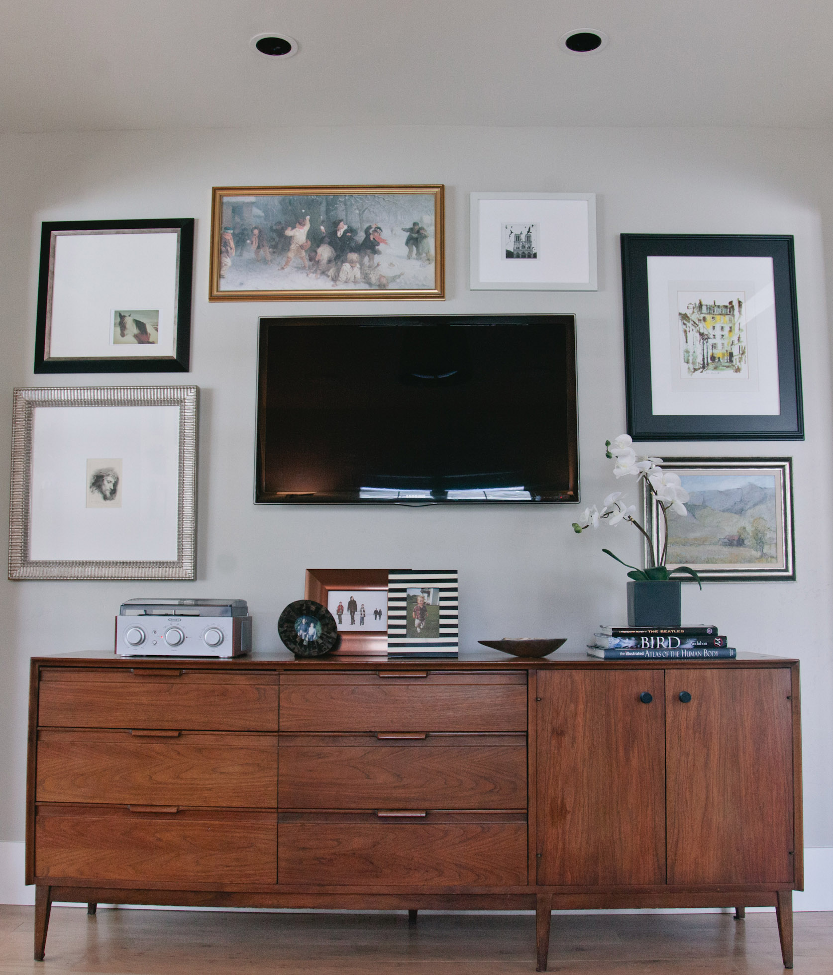 A mid-century modern credenza does double duty as a media console. The wall mounted TV blends in with the gallery of artwork which surrounds it.