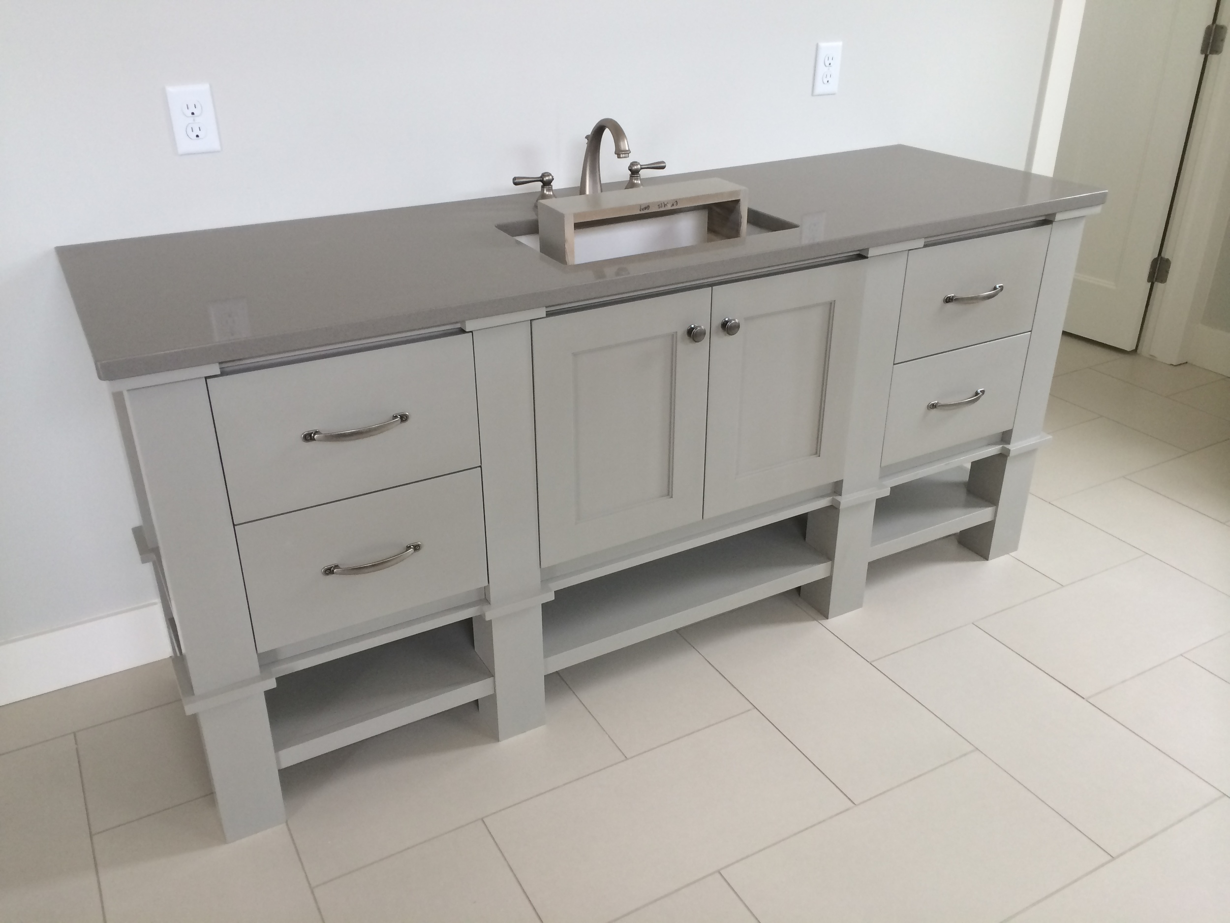 Multiple choices were made in this custom designed vanity including the obvious ones such as paint color, countertop, hardware, sink and faucet. The finer details include the height, width and depth of each drawer and door within the cabinet; the species of wood; the amount of open space and thickness of the wood for the open shelving; the door style and profile; and the decorative post detail.