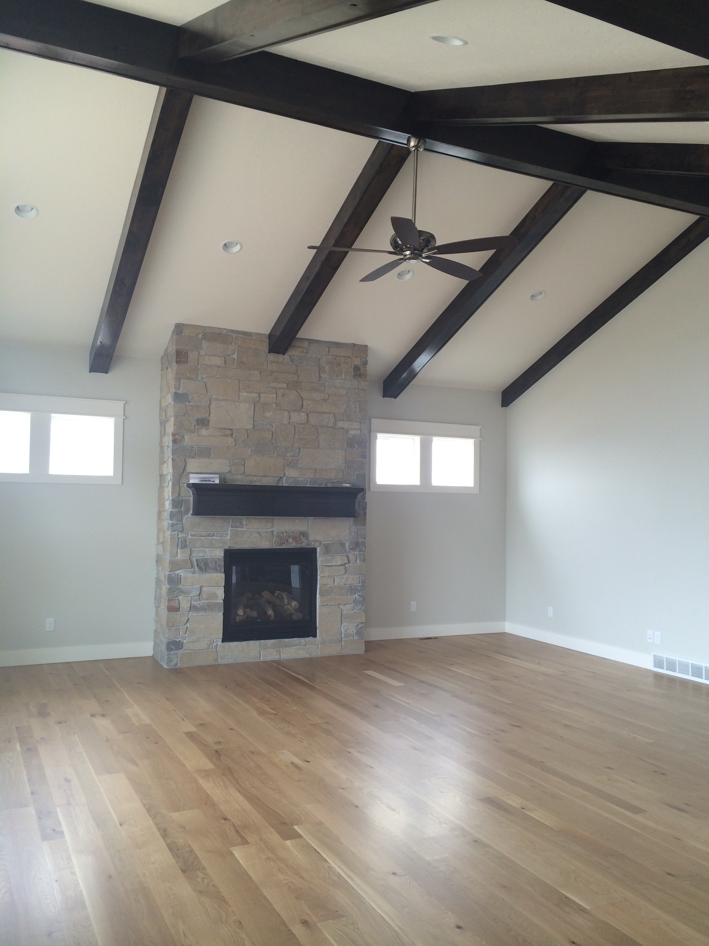 Faux beams highlight the vaulted ceiling. The beams and mantel were stained a charcoal color to pull out the dark knots and grain of the oak flooring. Notice the simple yet distinguished profile of the beams and the mantel.