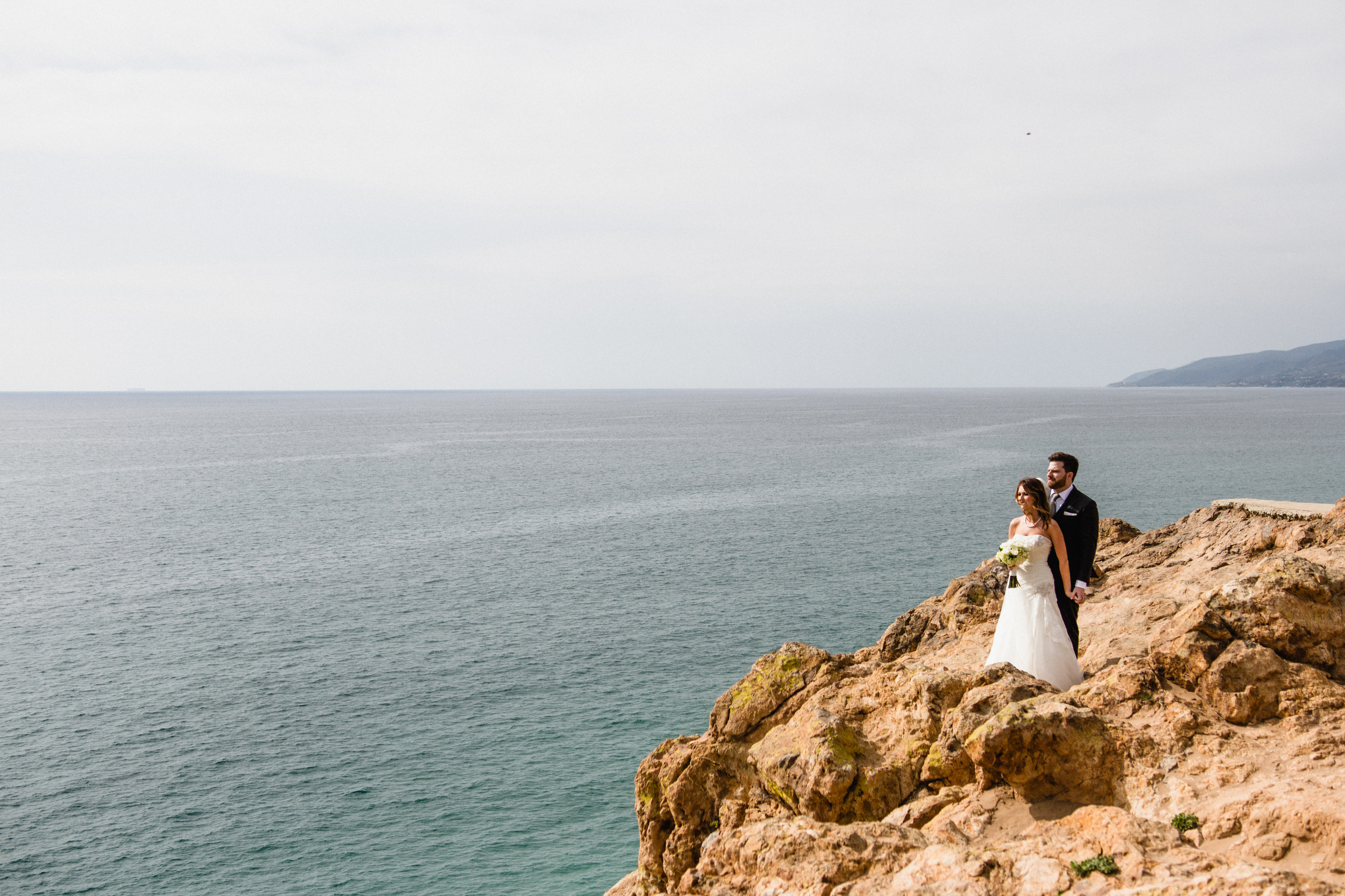 Point Dume Wedding Photography. Bride and Groom stare out at the ocean from the beach.