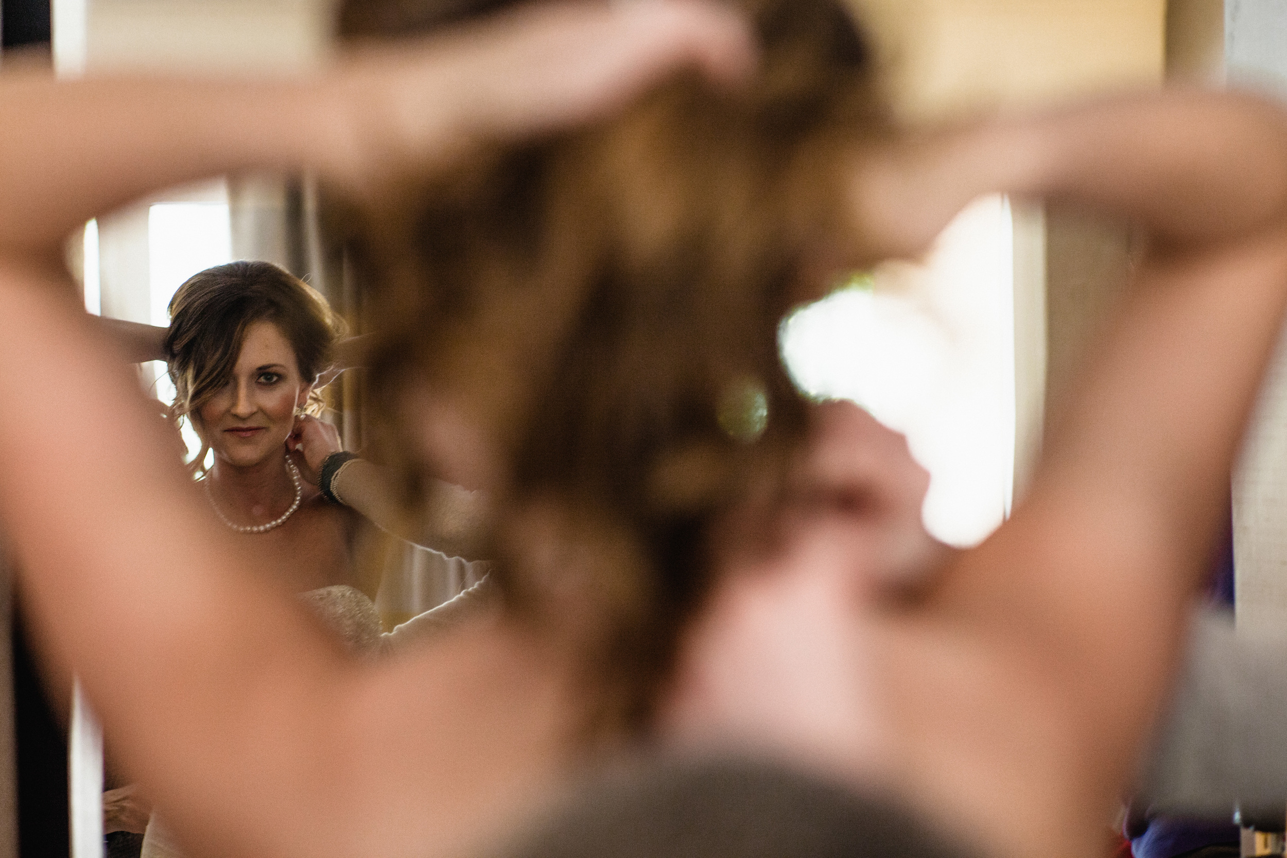 Wedding Photography. Bride gets ready with her bridesmaids in her hotel room before the wedding