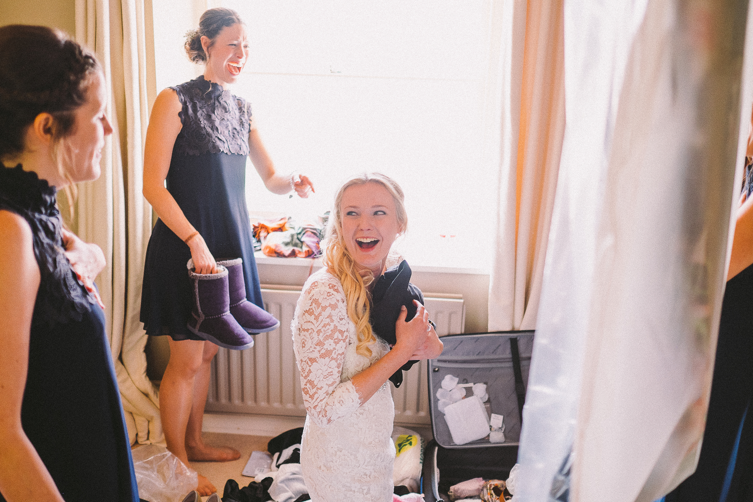 Bride clutching a bag, kneeling down among an open suitcase while one of her bridesmaids points and laughs.  Why would this be in a wedding album?