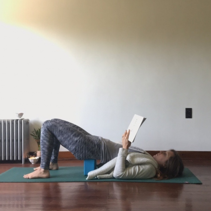 7.) Supported Bridge - Add a block or bolster under the back of the pelvis for this therapeutic inversion. Keep wrists over elbows to support any sized book.