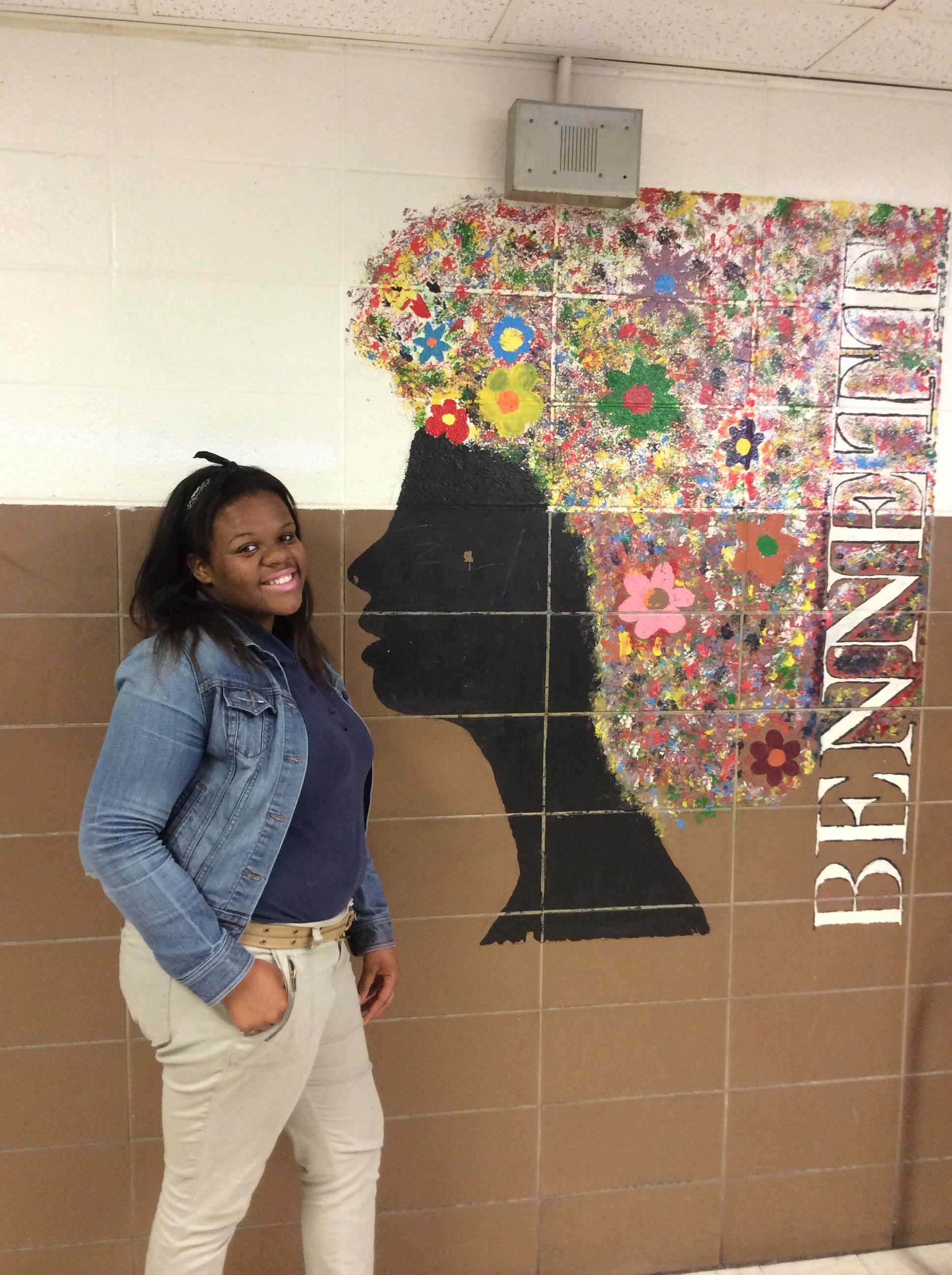 Dreonna at Ballou High School posing with am image of her next alma mater!