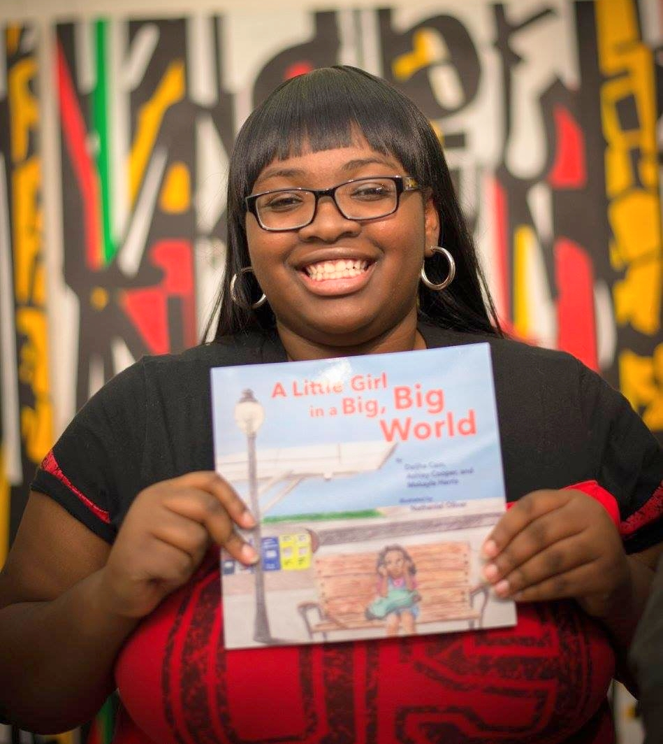 Daijha Cain shows off her new book at the Reach Book Launch.