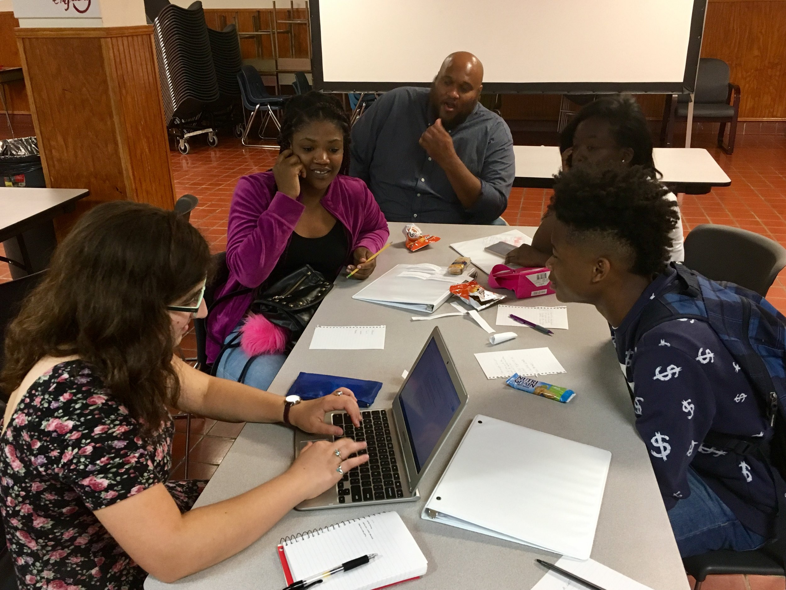 Eva (far left) writes with her group members Mikala, Makiya, and Dartavius. Reach Incorporated employee Vincent also listens in.