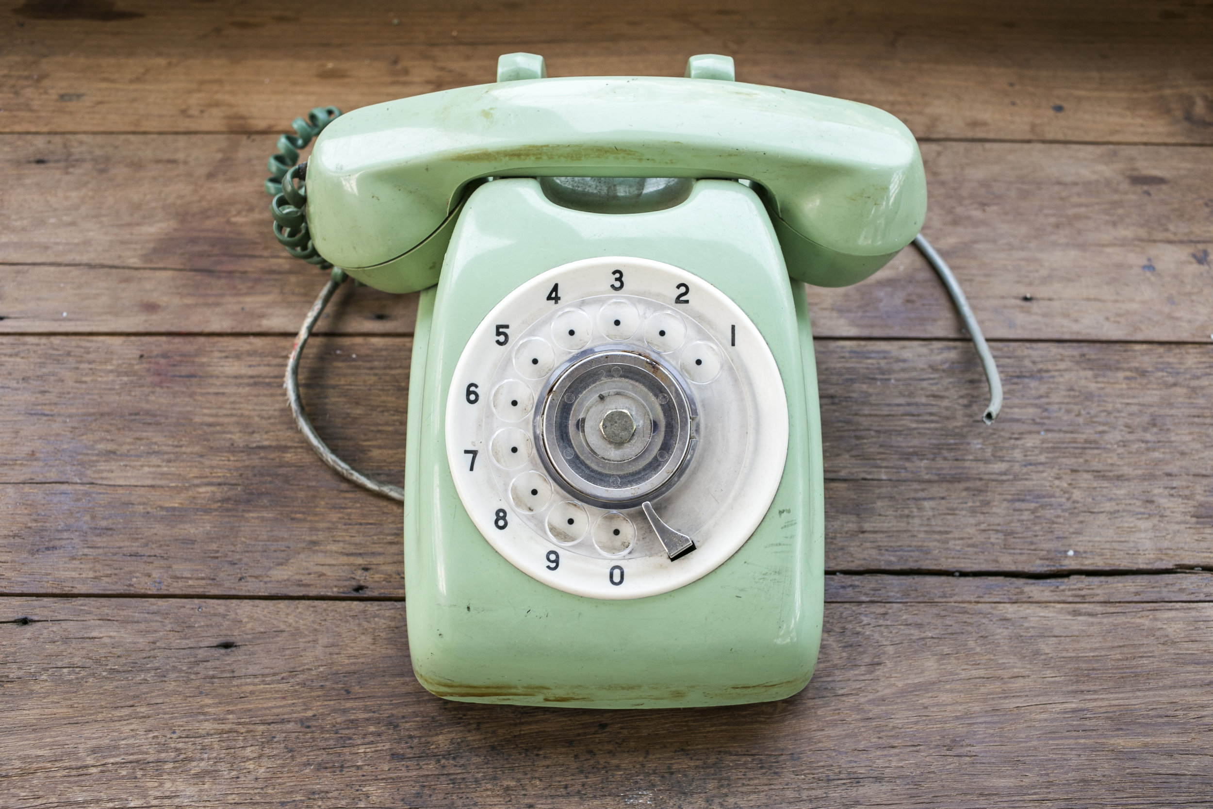 green-vintage-telephone-on-brown-wood-desk-background_BwJxPaeu3Gx.jpg