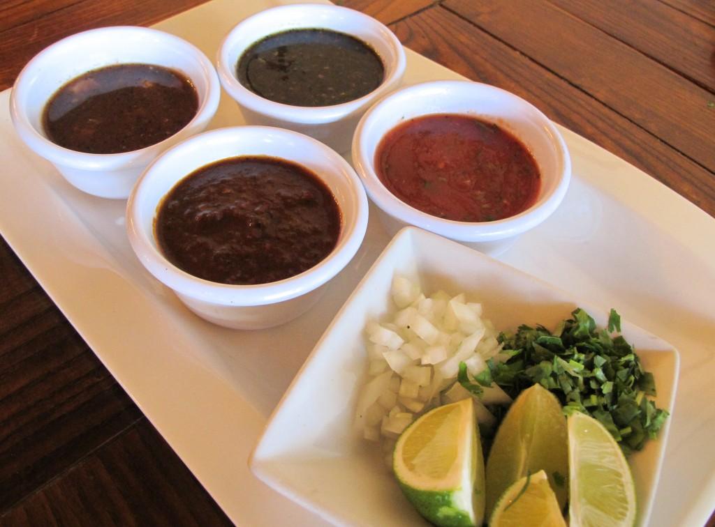 Top left - Salsa Habanero (habanero peppers, tomatoes, garlic, onions, cilantro) Top right - Salsa Quemada (roasted tomatoes, serrano peppers, garlic, onions and cilantro) Bottom left - Salsa Chipotle (roasted tomatoes, chipotle peppers, garlic, cilantro and oregano) Bottom right - Salsa Mild (tomatoes, oregano, garlic, serrano peppers and cilantro)