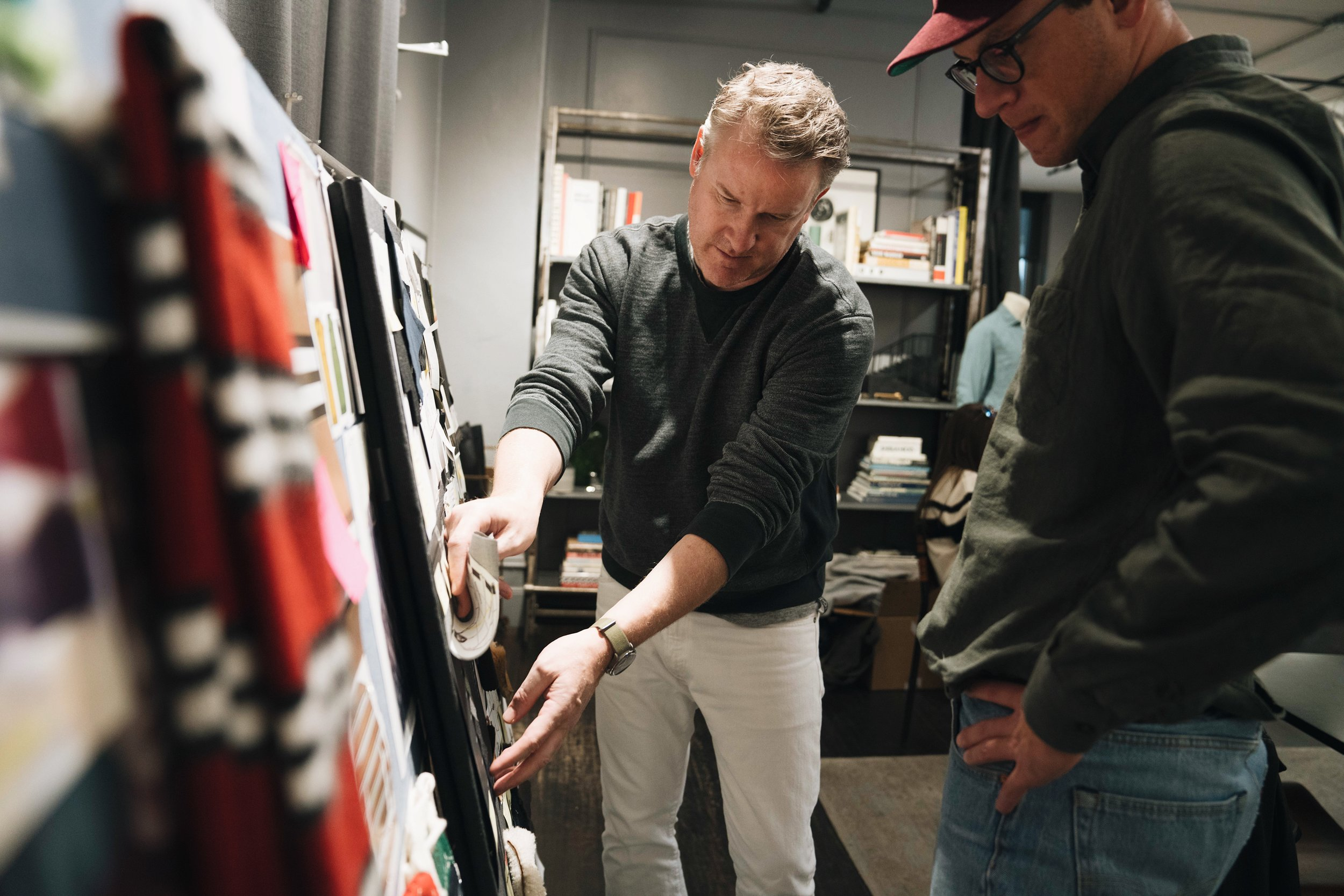 Discussing the upcoming collection on a mood board with one of his team members.
