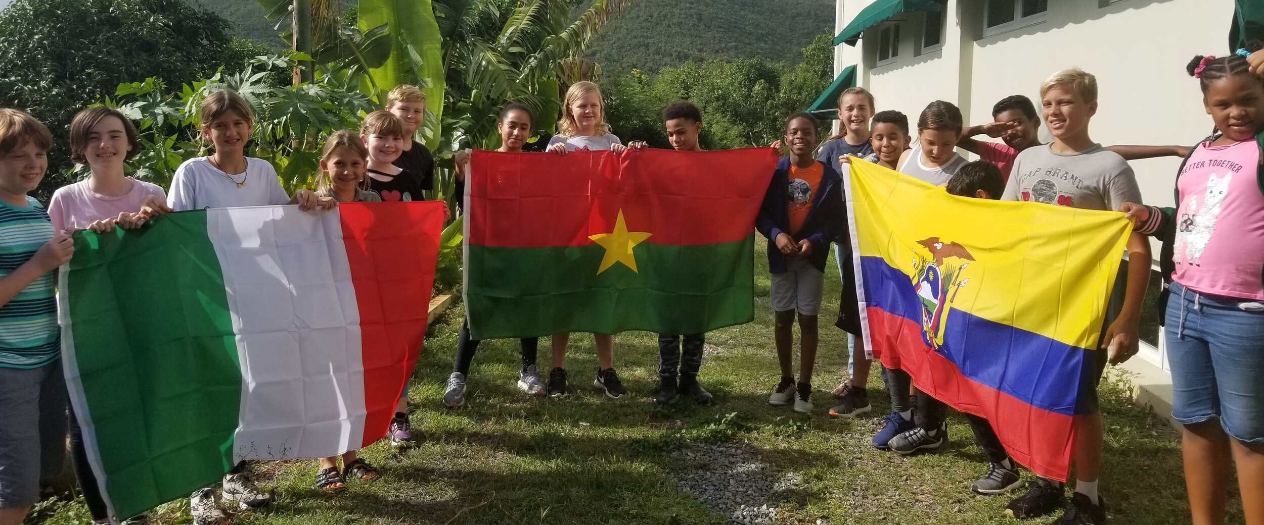 MMUN Students holding the flags of the countries to be represented. Left to right: Italy, Burkina Faso, Ecuador.
