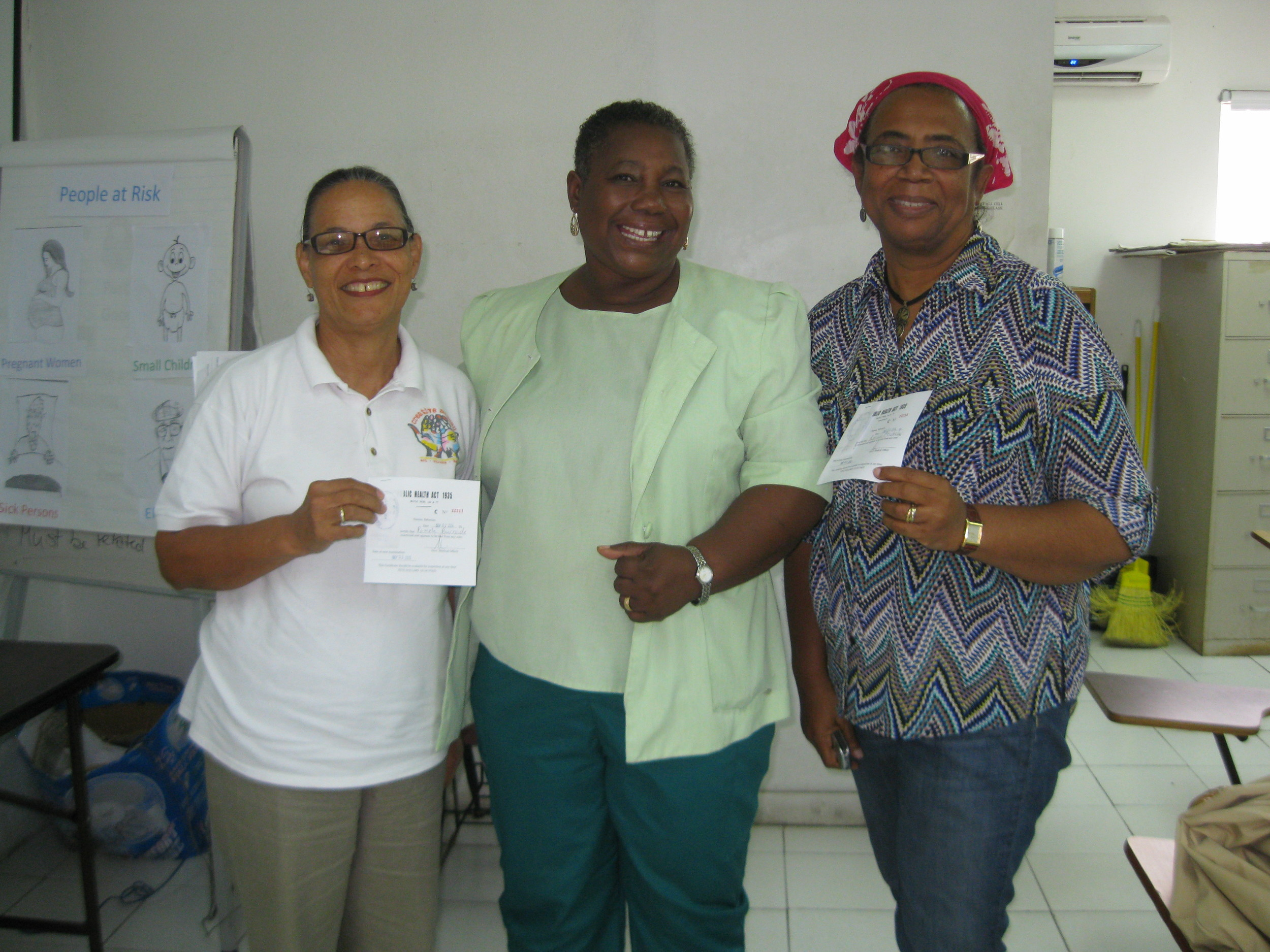 Pam (left) and Patricia (right) pose with their instructor, Nurse Turnquest (centre) after successful;y completing their Food Handlers Course for the CN Market