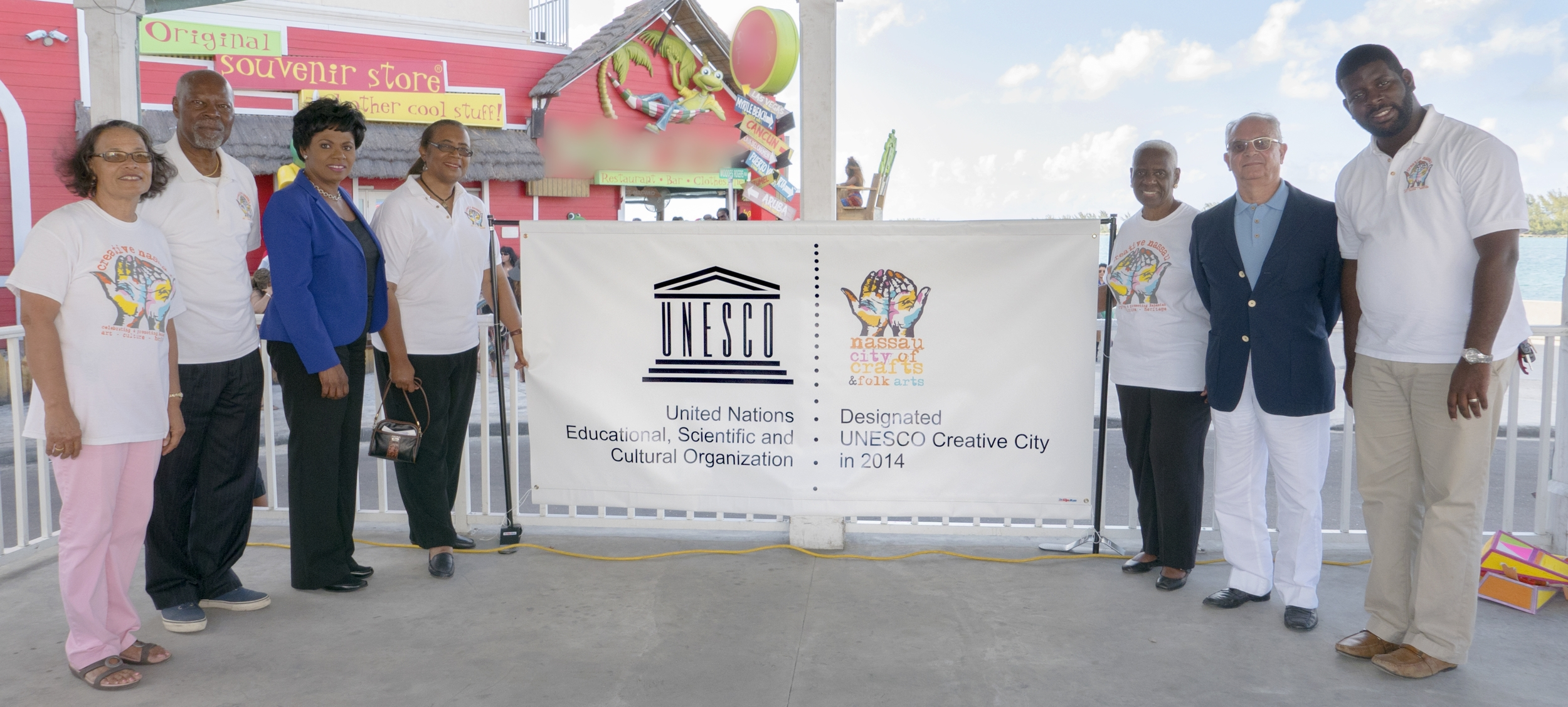 """Members of Creative Nassau, along with Executive Members of the Downtown Nassau Partnership officially unveiled the UNESCO Creative Cities Network Banner at the Creative Nassau Pompey Square Market in March 2015. Left to right: Pam Burnside CN President, Dr Davidson Hepburn, CN Secretary, Vernice Walkine DNP, Patricia Glinton Meicholas, CN Vice President, Rosemary Hanna, Charles Klonaris and """"Mayor"""" Gevon Moss of the DNP."""