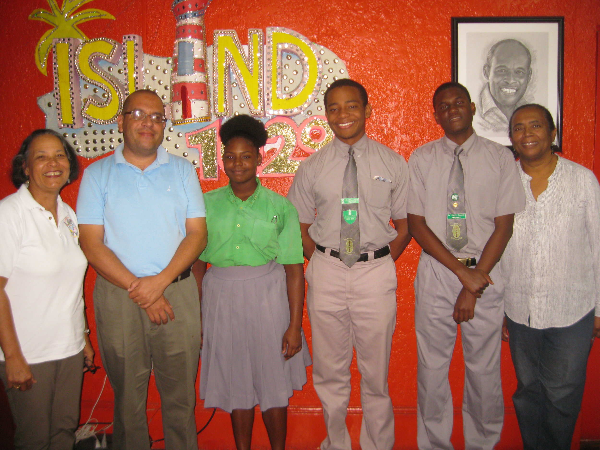 The radio studio photo shows (left to right): Pam, Father Turnquest, 11th Grade student Dwayna Archer, Head Boy and Team Leader Justyn Sweeting, 12th Grade student Richard Hanna and Patti.