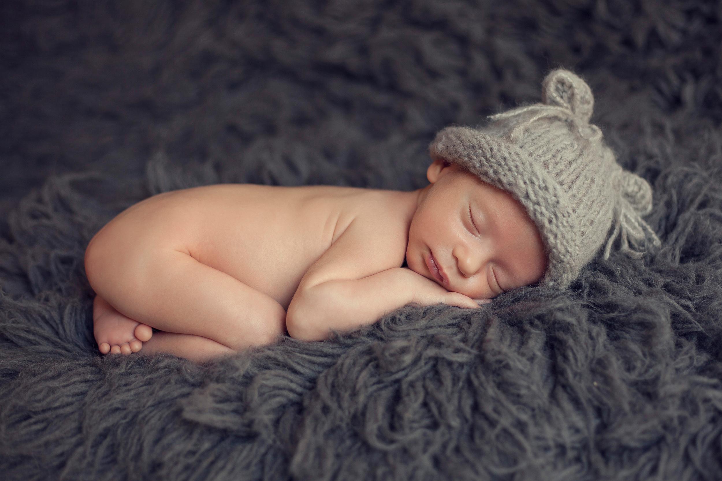 adorable tiny baby boy sleeping on grey flokati wearing kitten hat
