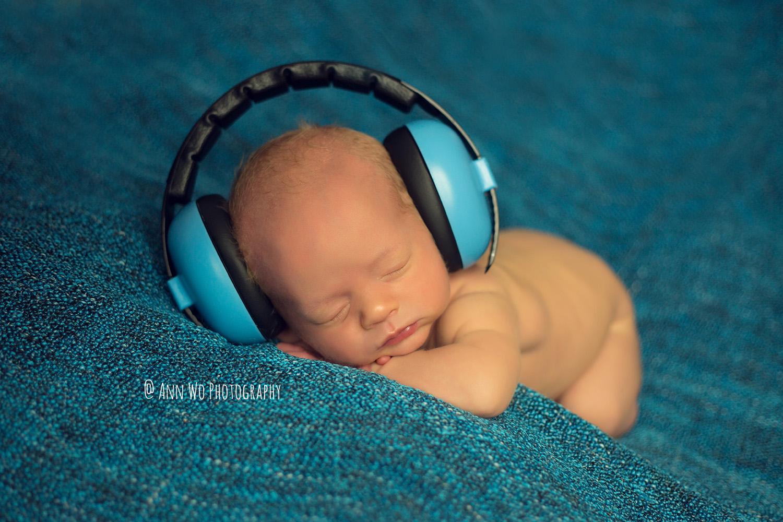 newborn baby boy with headphones sleeping on blue blanket