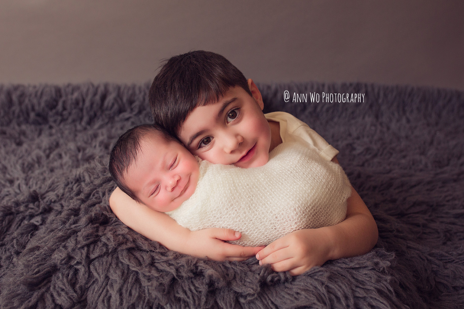 brother and newborn baby sister cuddle adorable flokati ann wo london