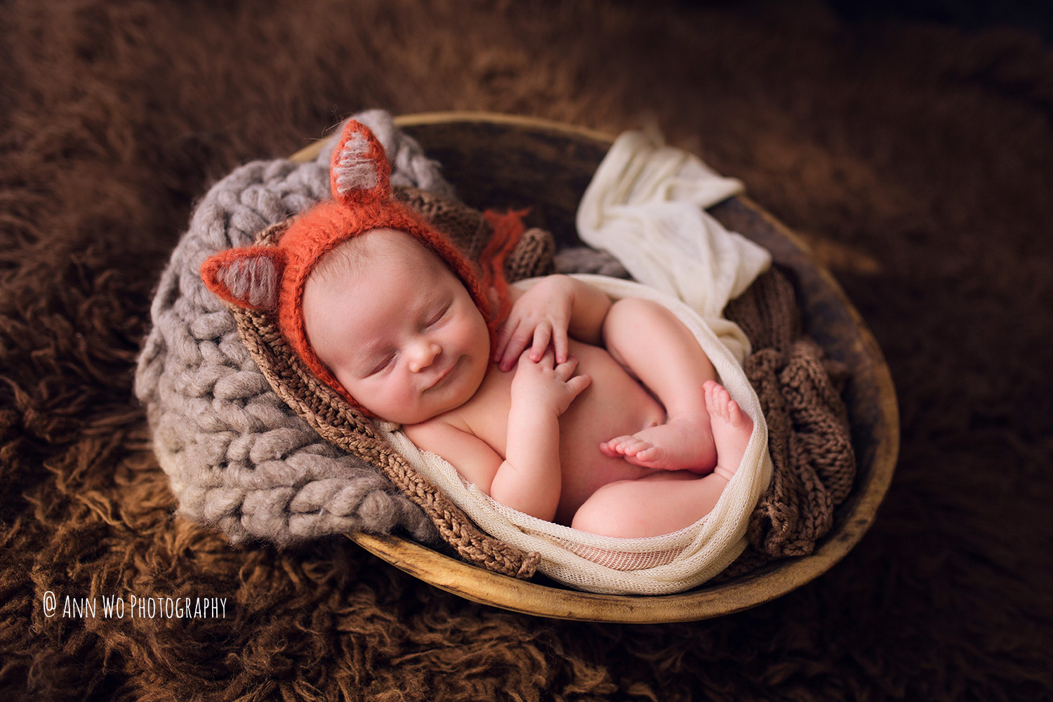 newborn photographer in London Ann Wo baby boy sleeping wrapped in a wooden bowl wearing knitted fox hat