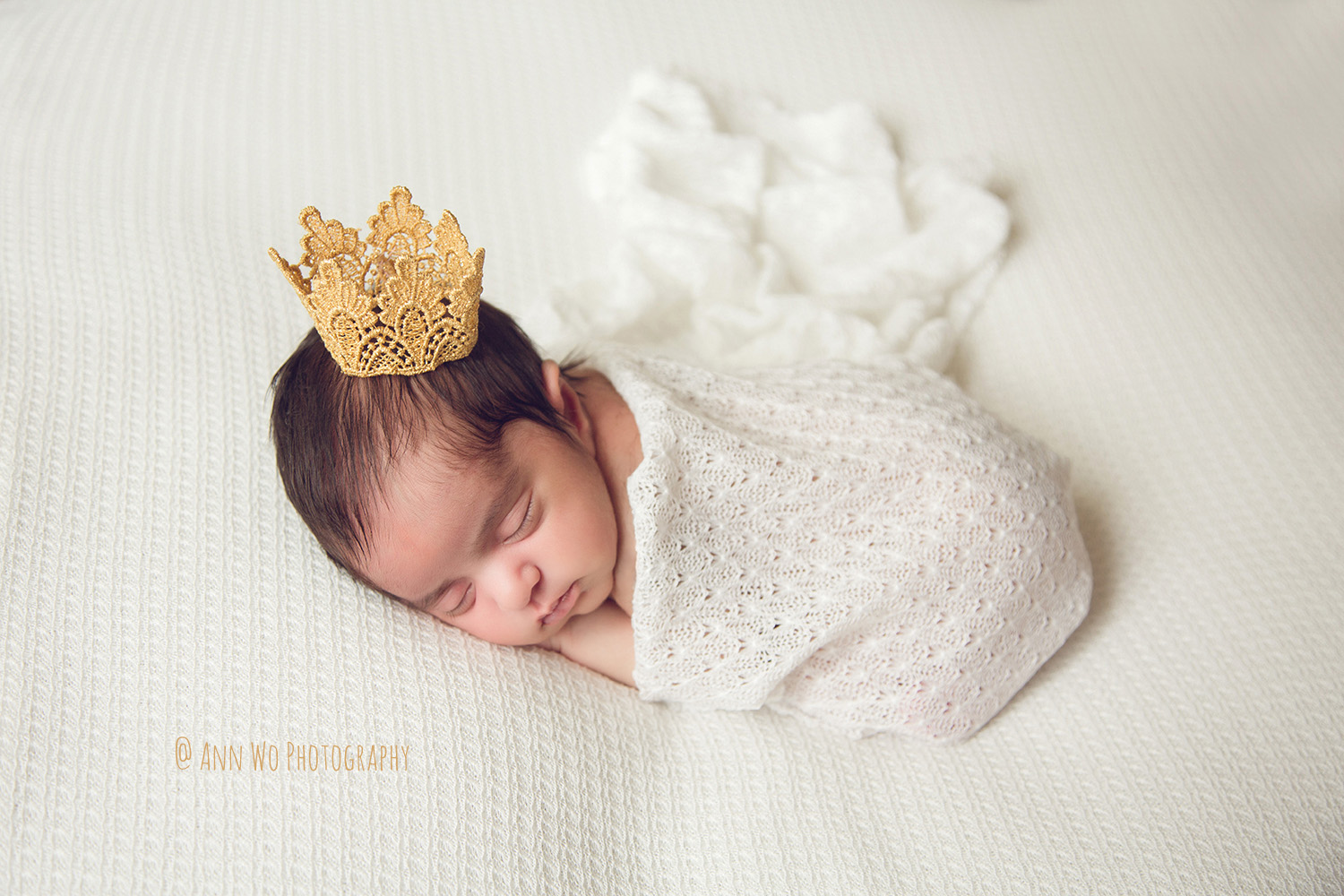 Newborn photography in London white lace setup with golden crown Ann Wo