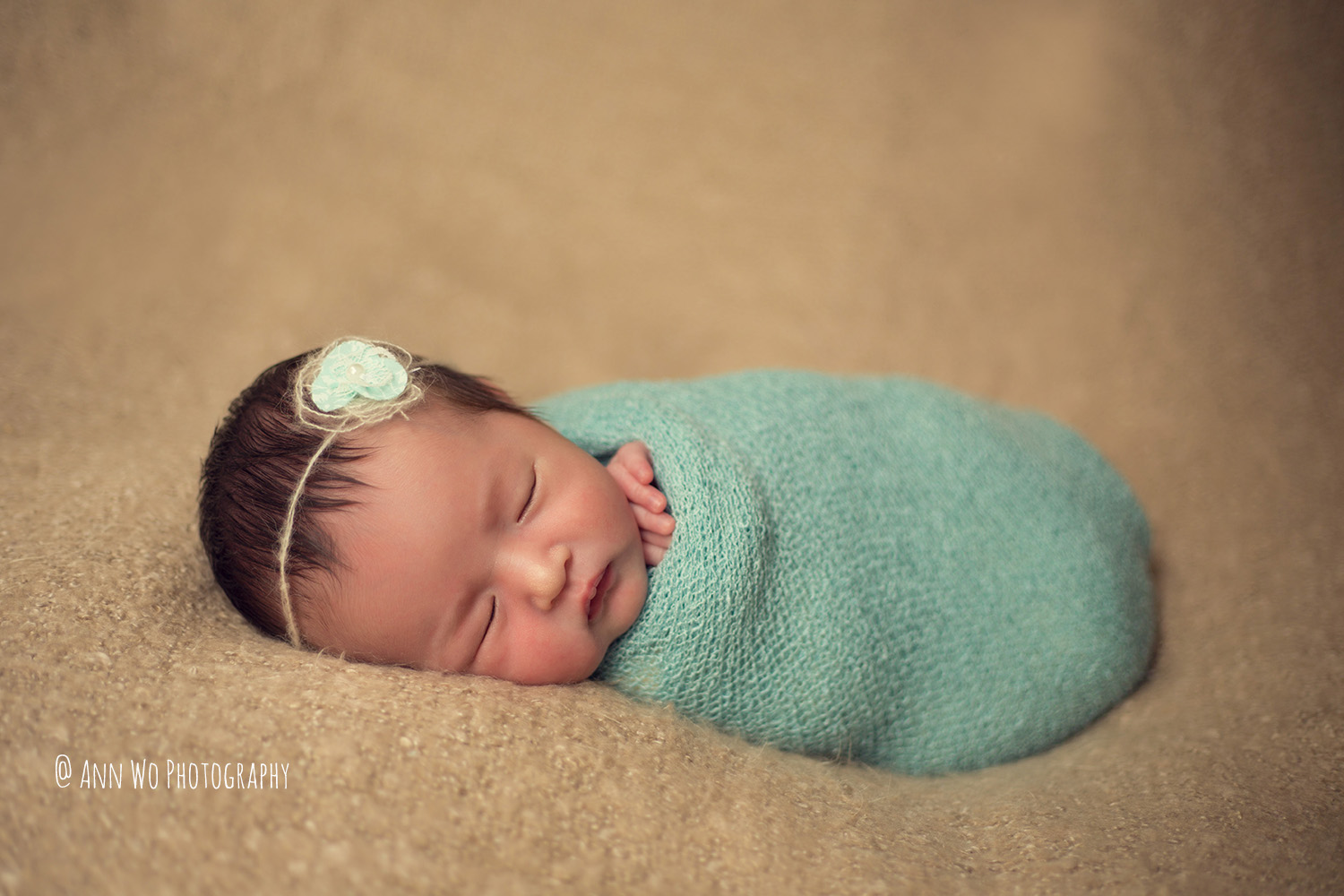 green wrap and beige blanket newborn photography in London by Ann Wo