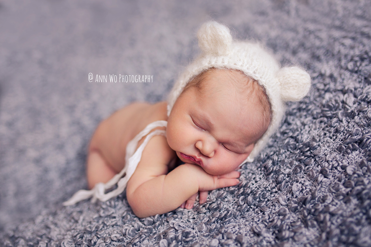 Newborn photographer in London UK Ann Wo thick grey blanket and soft bear bonnet Ann Wo